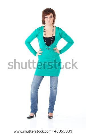 Cute young adult caucasian woman wearing a Turquoise top and a beaded necklace with blue jeans and with short brunette hair on a white background. Not Isolated - stock photo