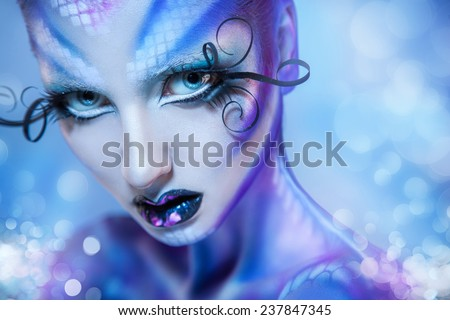 Cute young adult girl looking at camera with creative body art and bokeh on background in studio - stock photo