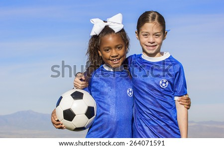 Cute, young african american and hispanic female soccer players holding a ball with a simple blue sky background - stock photo