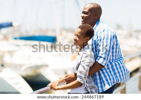 cute young african american couple daydreaming at the harbor - stock photo