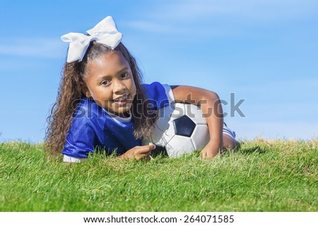 cute, young african american girl soccer player holding a ball laying on a grass field with a simple blue sky background. Lots of room for copy space - stock photo