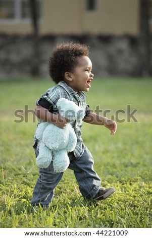Cute young African American toddler walking on a field of grass - stock photo