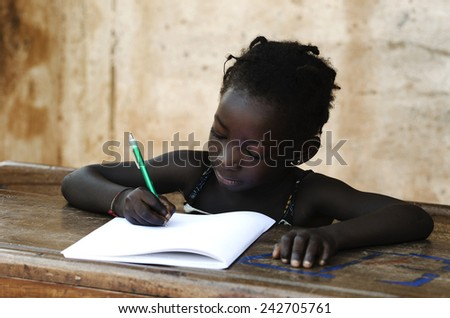 Cute Young African Girl At School With Her Exercise Book - stock photo