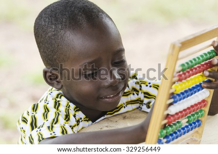Cute Young African Schoolboy Learning to Count with an Abacus in his school in Bamako, Mali. - stock photo