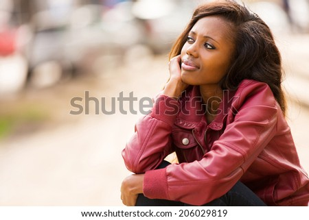 cute young african woman daydreaming outdoors - stock photo