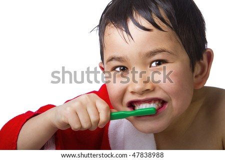 Cute young asian boy brushing his teeth fresh out of the shower isolated on white background