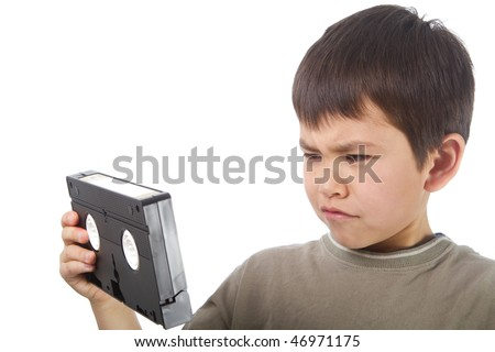 Cute young asian boy seems confused by a video cassette tape.  A metphor for how fast technology changes - stock photo