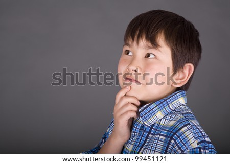 Cute young asian boy with mischievous smile and wearing casual clothes on a grey background - stock photo
