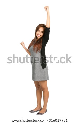 Cute young Asian girl in gray dress, black sweater raising her arm, pumping her fist, quietly celebrating, cheering a goal. Thai national of Chinese origin. Full length