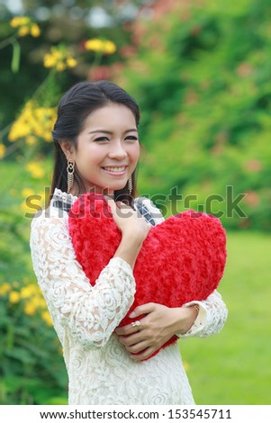 Cute young Asian woman holding a red heart-shaped pillow. - stock photo