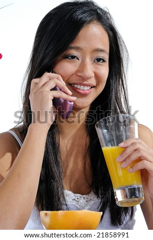 Cute young Asian woman on phone at breakfast