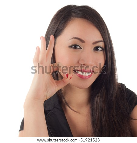 Cute young asian woman smiling and showing okay sign with finger and thumb - stock photo