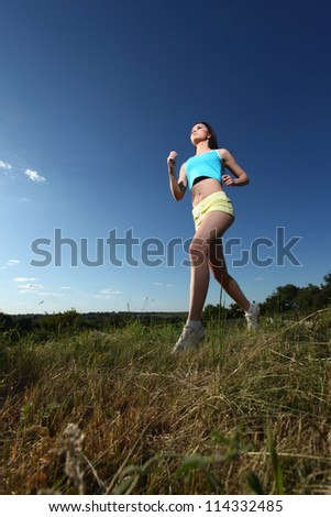 Cute young athletic woman running through the green grass against the blue sky - stock photo
