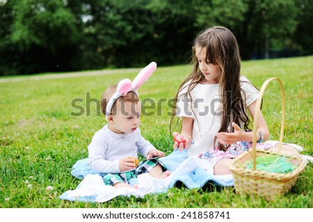 Cute young baby  brother and school aged sister playing with Easter eggs outside in the park together. - stock photo