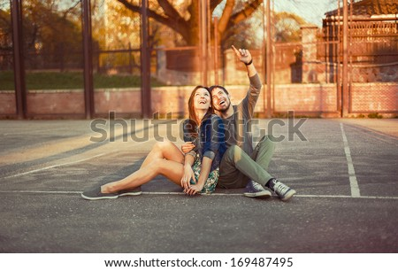 Cute young beautiful couple sitting on the ground in city near university after studying and having fun together laughing and smiling  - stock photo