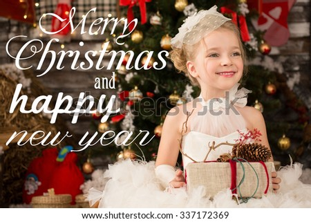 Cute Young beautiful girl in white Christmas dress is taking Christmas gift. She has white voile on her head. There is Christmas tree in the background.  Vintage holiday card or invitation.?-mas card. - stock photo