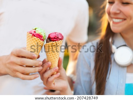 Cute young beautiful teen couple in city near university with ice cream after studying and having fun together laughing and smiling