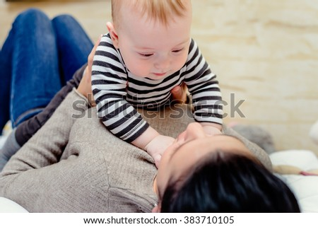 Cute young blond baby playing with its mother as she lies on her back on a duvet clambering over her with a happy smile, close up view of the face - stock photo
