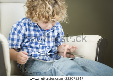 Cute Young Blond Boy Using His Computer Tablet in a Chair. - stock photo