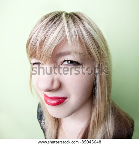 Cute young blond girl with wrinkled nose - stock photo