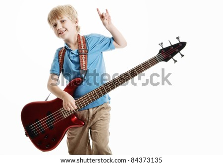 Cute young blond haired boy playing an electric guitar against a white background