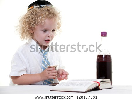 Cute young blond toddler jewish boy playing pretend - stock photo