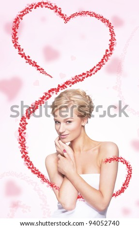 Cute young blond woman holding flying heart