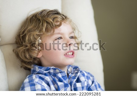 Cute Young Blonde Boy Daydreaming and Sitting in Chair. - stock photo