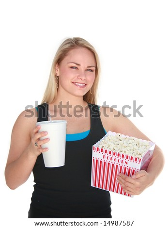 Cute young blonde woman holding large box of popcorn and a coke.