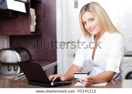 cute young blonde woman paying with credit card