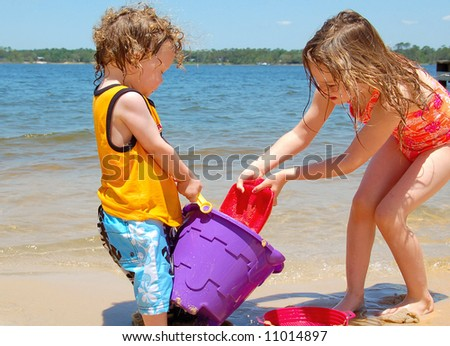 Cute young boy and girl playing in sand on seashore - stock photo