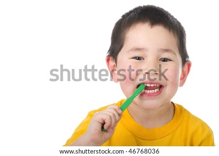 Cute young boy brushing his teeth isolated on white background - stock photo