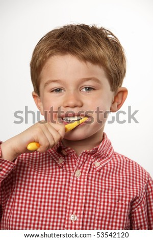 cute young boy brushing teeth with positive expression
