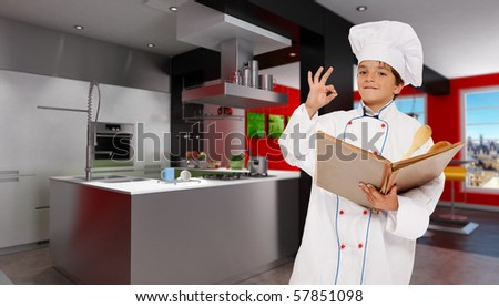 Cute young boy dressed as a chef in a modern kitchen holding a book