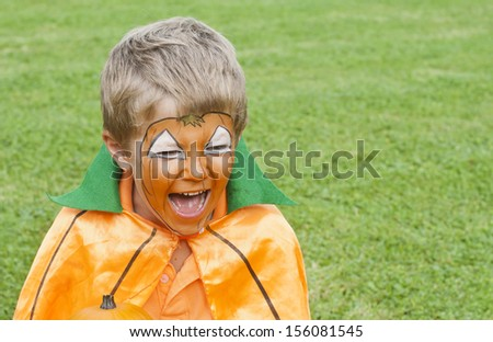 Cute, young boy dressed as a pumpkin for Halloween - stock photo