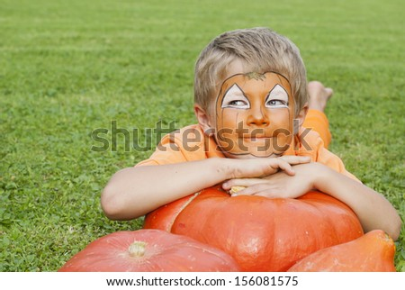 Cute, young boy dressed for Halloween lying on a pumpkin - stock photo