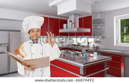 Cute young boy dressed in chef clothes, holding a book, doing the ok sign on a kitchen interior