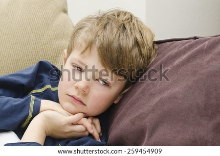 Cute young boy feeling ill and lying down - stock photo