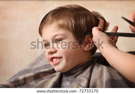 cute young boy getting a haircut - stock photo