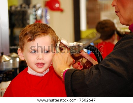 Cute Young Boy Getting Haircut at Barber - stock photo
