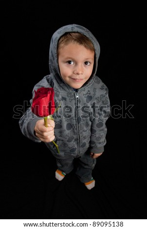 cute young boy giving  a rose to the viewer - stock photo