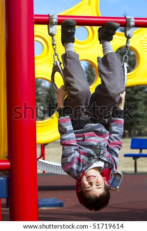 Cute young boy hanging upside down on a playgroung structure