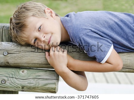 Cute young boy holding onto a fence in a field - stock photo