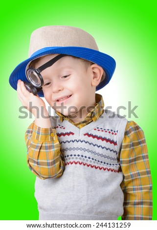 cute young boy in a hat and glasses on green background - stock photo