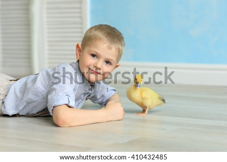 cute young boy in a striped shirt lying on the floor next to the yellow duckling. Easter - stock photo
