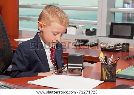 Cute young boy in business clothing in a business office.