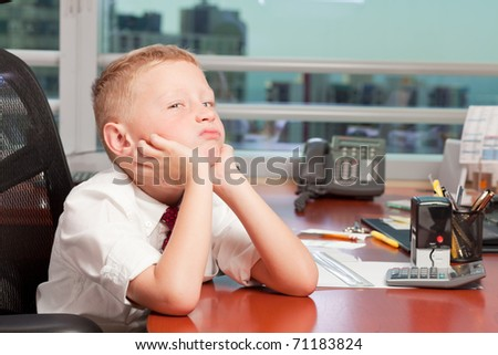 Cute young boy in business clothing in a business office with a bored expression.