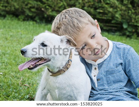 Cute, young boy in the garden holding a dog - stock photo