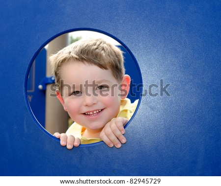 Cute young boy kid or child peeks through hole at playground outdoors at park. - stock photo