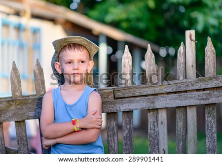 Cute Young Boy Leaning Against the Wooden Fence with Arms Crossed Over his Stomach, Showing a Pensive Facial Expression. - stock photo